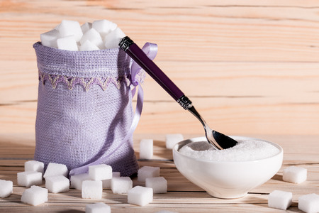 sugar cubes: White sugar cubes in a bag on wooden background Stock Photo