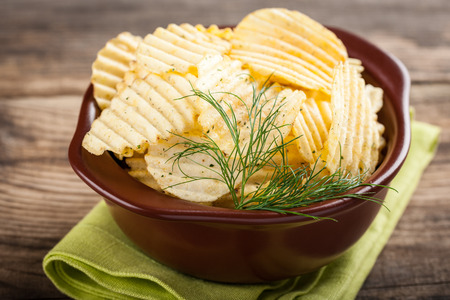 potato: Potato chips in bowl on wooden background