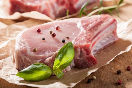 pork chop: Raw pork chop on wooden table