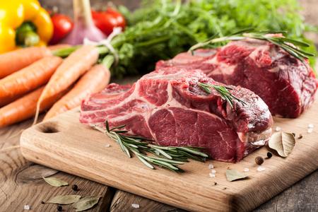 carnes rojas: Carne de vaca sin procesar a bordo y verduras frescas del corte en mesa de madera Foto de archivo