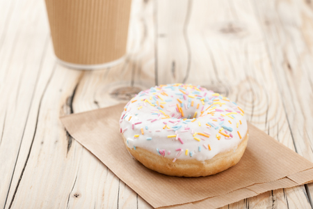 paper cup: Donut and paper cup on wooden table, close up