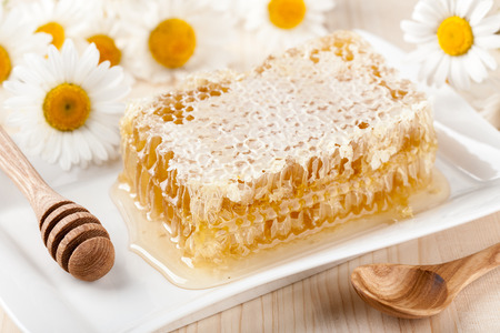 honey comb: Honey comb and chamomile flowers on wooden table