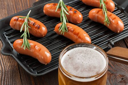grilled sausages: Grilled sausages and beer on wooden table Stock Photo