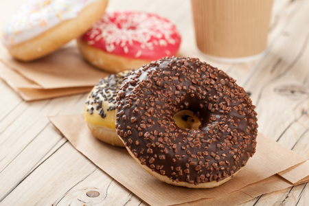 paper cup: Colorful donuts and paper cup on wooden table, close up Stock Photo