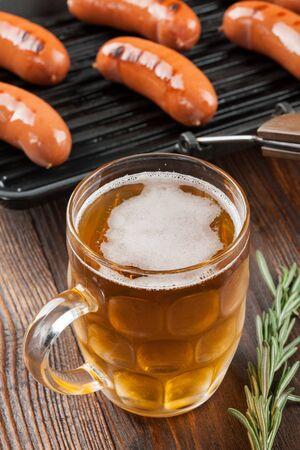chorizos asados: Salchichas a la parrilla y cerveza en mesa de madera Foto de archivo