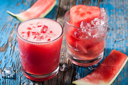 watermelon juice: Glass of watermelon juice with ice and watermelon heart in the glass on wooden table