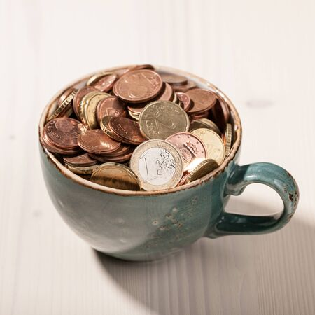 euro coins: Euro coins in the ceramic cup on wooden table Stock Photo