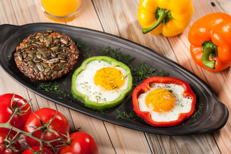 fried eggs: Breakfast with fried eggs, peppers, tomatoes, orange juice and bread