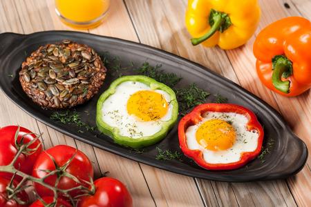 huevos estrellados: Desayuno con huevos fritos, pimientos, tomates, jugo de naranja y pan Foto de archivo