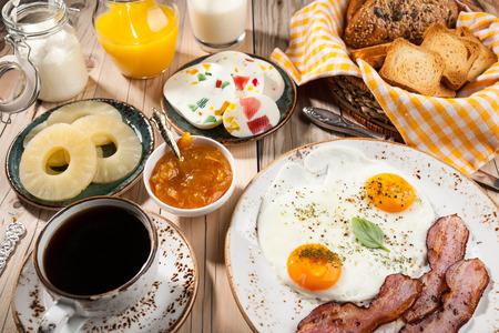 Prima colazione con uova fritte, pancetta, caffè, formaggio, marmellata, ananas, succo di frutta, pane