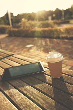 paper cup: Digital tablet and paper cup on wooden bench in sunshine