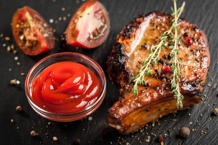 Dish of grilled pork chop with steamed vegetables and sauce
