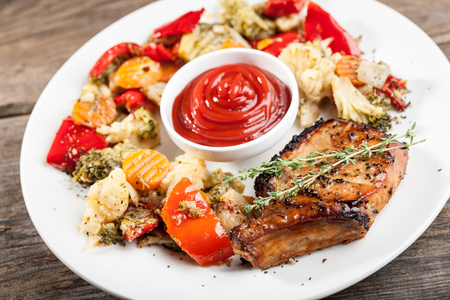 grilled pork chop: Dish of grilled pork chop with steamed vegetables and tomato sauce