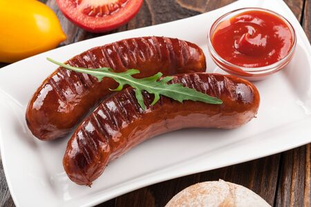 chorizos asados: Grilled sausages with tomato sauce, tomatoes and bread Foto de archivo