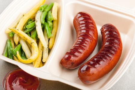 chorizos asados: Salchichas a la parrilla con frijoles franc�s en la lonchera y el taz�n de salsa de tomate en la mesa