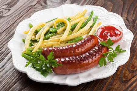 chorizos asados: Salchichas a la parrilla con frijoles fritas y salsa de tomate en un plato
