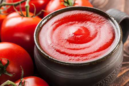 Tomato sauce in a ceramic bowl and red tomatoes