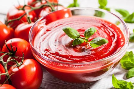 salsa de tomate: Salsa de tomate con hojas de albahaca en un recipiente de vidrio y tomates rojos Foto de archivo
