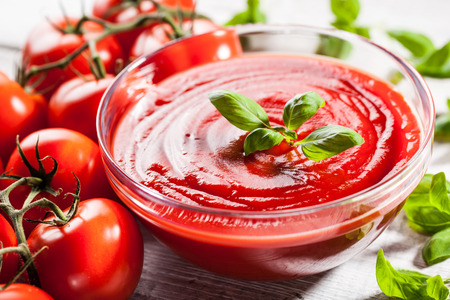 Tomato sauce with basil leaf in a glass bowl and red tomatoes Standard-Bild