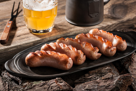chorizos asados: Grilled sausages on ceramic plate and mugs of beer on wooden table