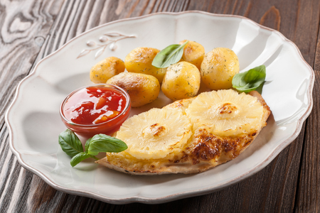 chicken fillet: Meal of grilled chicken fillet with pineapples and baked potatoes