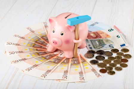 banconote euro: Piggy Bank con un martello, banconote e monete in euro Archivio Fotografico