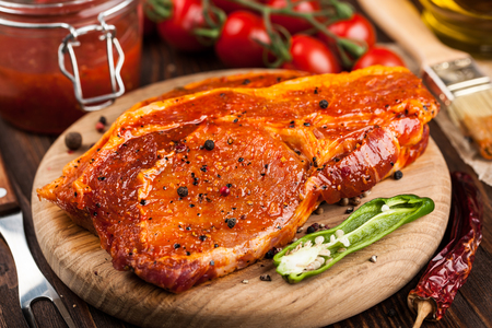 barbecue pork barbecue: Marinated pork steaks on cutting board and ingredients  for cooking Stock Photo