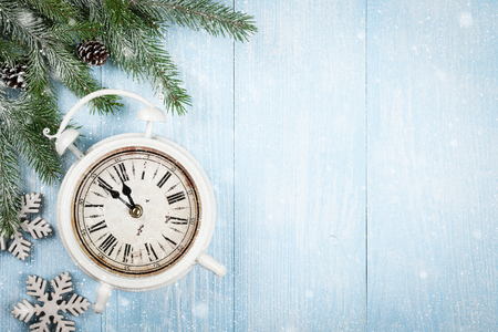 fir cones: Fir tree with fir cones and alarm clock in snow on blue wooden background