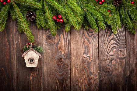 fir  tree: Decorated fir tree and birdhouse on dark brown wooden background