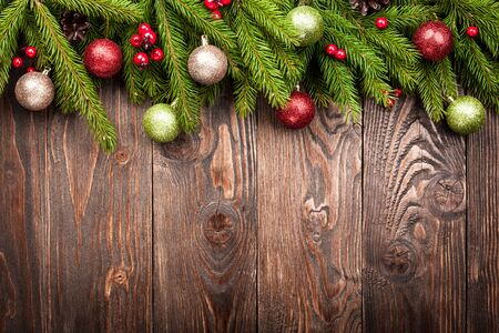 red berries: Fir tree decorated balls, cones and red berries on dark brown wooden background Stock Photo