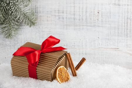 dried orange: Christmas and New Year gift box with red bow, cinnamon sticks, dried orange on the snow Stock Photo