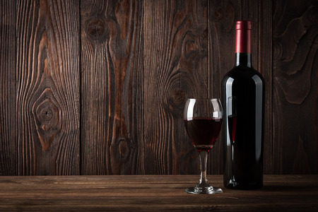 Red wine bottle and glass of wine on the dark wooden background, studio light Stock Photo