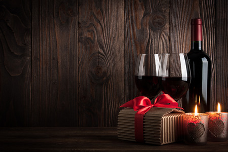 wine gift: Red wine bottle, two glasses of wine, gift box and candles on the dark wooden background