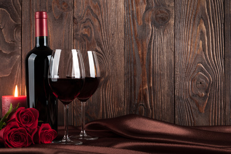 Red wine bottle, two glasses of wine, candle and red roses on brown silk Stockfoto