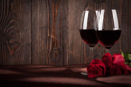 vino: Dos vasos de vino tinto y rosas rojas en la seda de color marrón