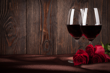 happy valentines: Two glasses of red wine and red roses on brown silk Stock Photo