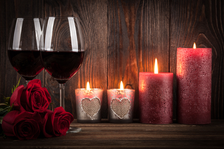 wine glasses: Two glasses of red wine, roses and candles on the dark wooden background Stock Photo