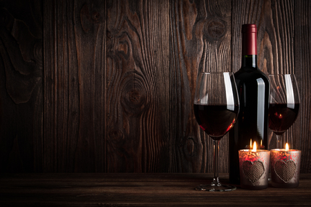 light in dark: Red wine bottle, two glasses of wine and candles on the dark wooden background, studio light