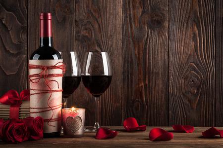 bebiendo vino: Botella de vino tinto, dos vasos de vino, caja de regalo, velas y rosas rojas en el fondo de madera oscura Foto de archivo