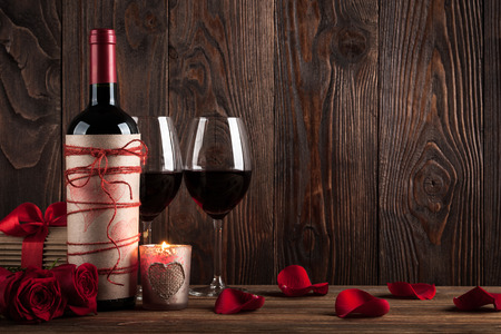Red wine bottle, two glasses of wine, gift box, candle and red roses on the dark wooden background