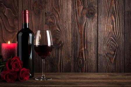 Botella de vino tinto, una copa de vino, velas y rosas sobre fondo de madera