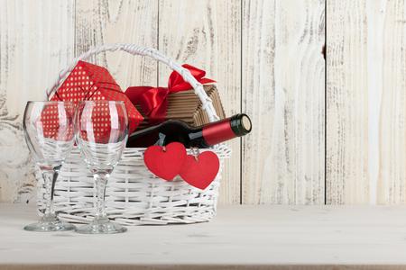 Korb mit Weinflasche, Geschenk-Boxen und Weingläser auf Holztisch