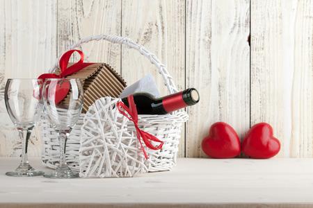 Korb mit Weinflasche, Geschenk-Box und Weingläser auf Holztisch