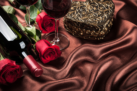 wine gift: Red wine bottle, two glasses of wine, gift box and red roses on the dark brown silk Stock Photo