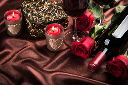 wine gift: Red wine bottle, two glasses of wine, gift box, candles and red roses on the dark brown silk