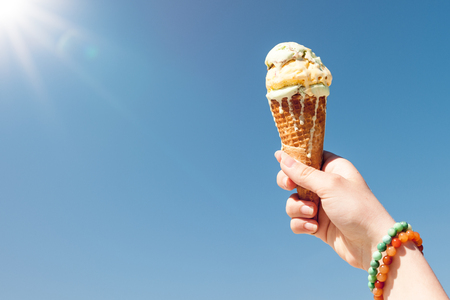 Hand holding ice cream cone on the sky background