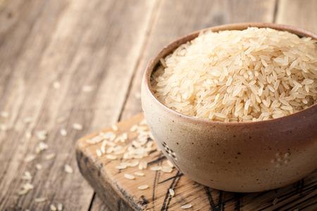 Ungekochter parboiled Reis in einer Schüssel auf Holztisch Standard-Bild - 82563671