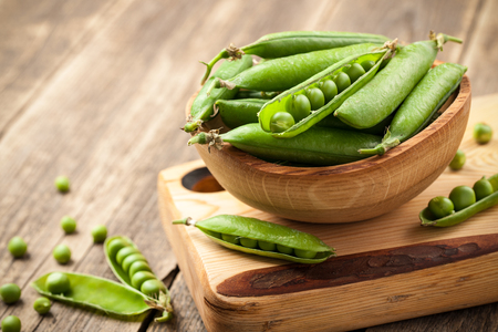 Ripe peas in a wooden bowl on wooden table