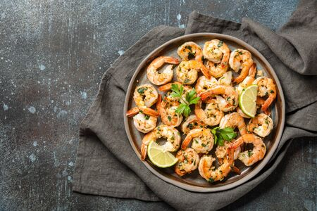 Grilled shrimps with garlic and parsley on ceramic plate