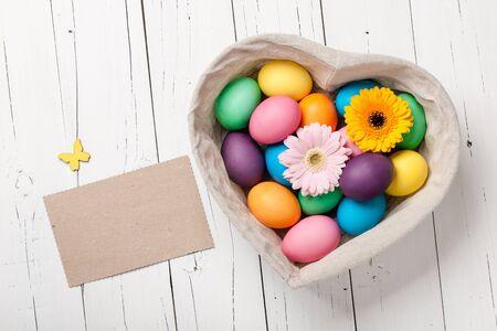 Easter eggs and gerbera flowers in heart shaped basket